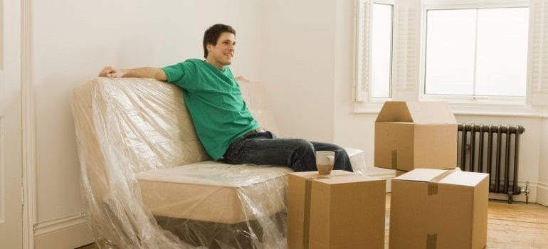 Person sitting in the room with moving boxes