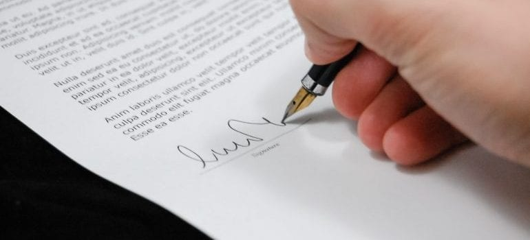 person signing a contract to avoid hidden costs of moving