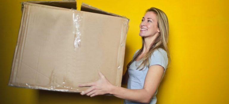 Woman in grey shirt carrying cardboard box and preparing to reuse moving boxes