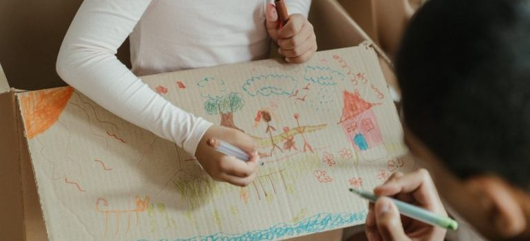 Children drawing on moving boxes