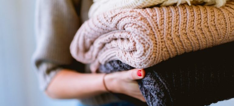 woman holding sweaters